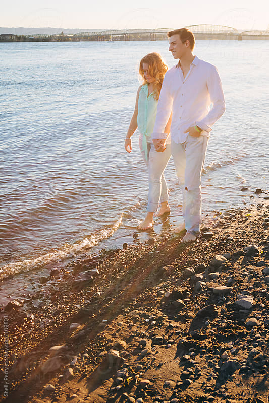 Couple walking at the waters edge by Shelly Perry for Stocksy United