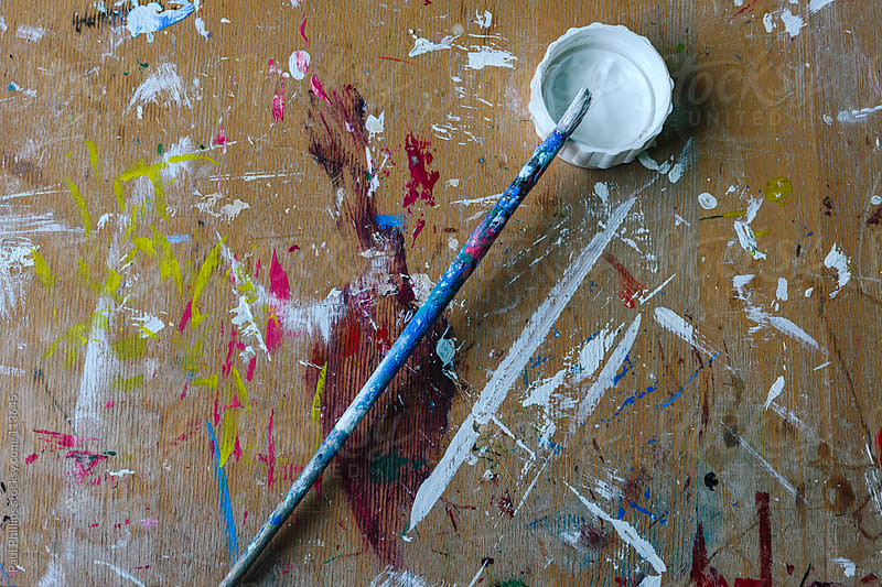 Single used paint brush laying on a school art desk top by Paul Phillips for Stocksy United