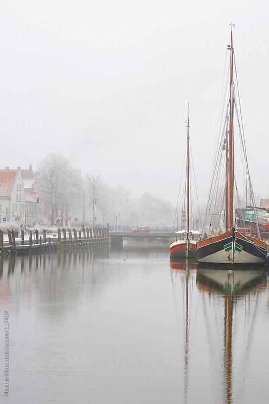 Boats on a river in winter by Melanie Kintz for Stocksy United
