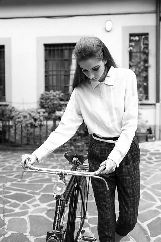 Fashionable woman holding a vintage bicycle by michela ravasio for Stocksy United
