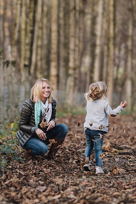 cute little girl with her mother having fun in autumnal forest by Leander Nardin for Stocksy United