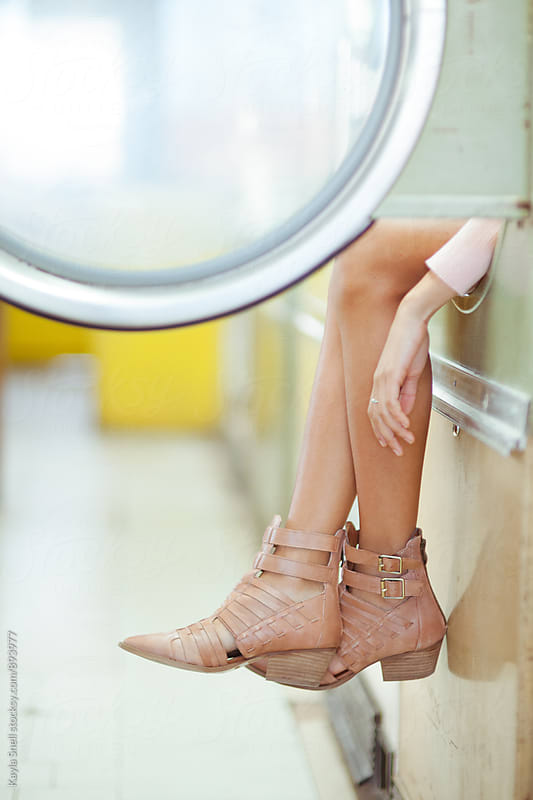 Woman at laundromat by Kayla Snell for Stocksy United