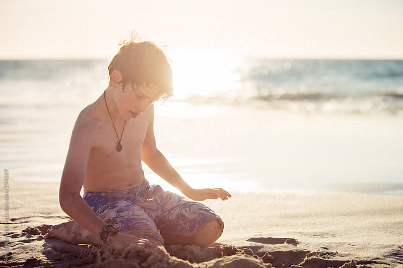 Boy playing in the sand at sunset by Angela Lumsden for Stocksy United
