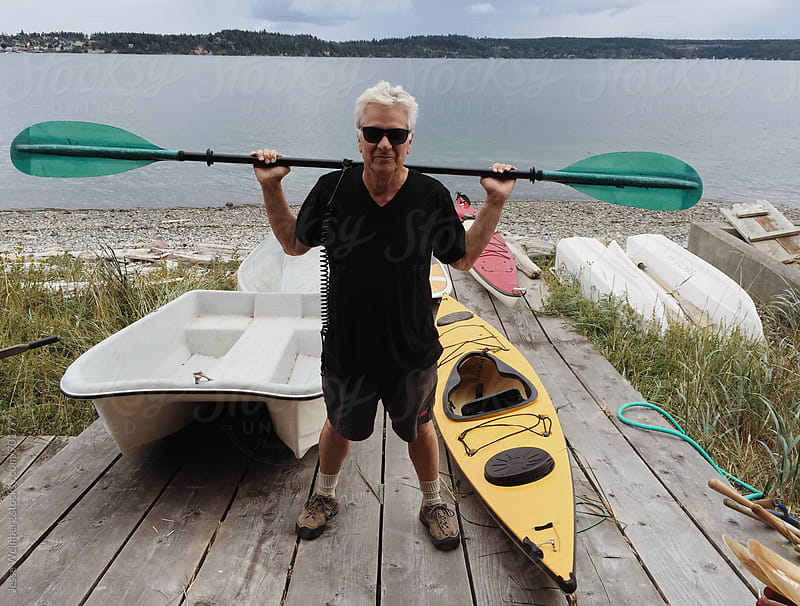 Man With Grey Hair Standing in Front of Boats by Jesse Weinberg for Stocksy United