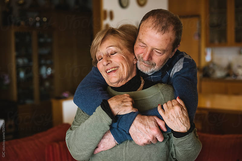 Happy and playful senior couple together at home by GIC for Stocksy United