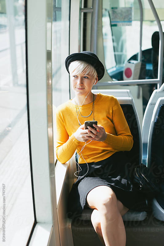 Modern and chic woman using her smartphone sitting in the train. by BONNINSTUDIO for Stocksy United
