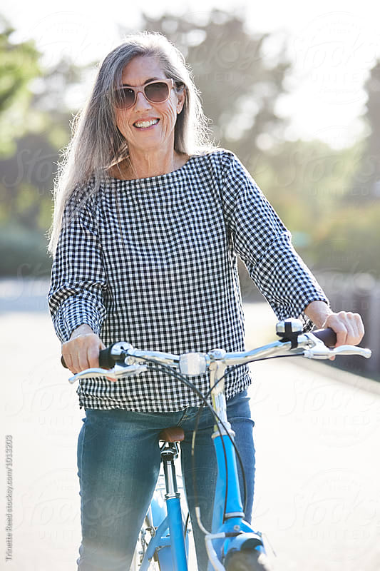 Portrait of stylish mature woman with grey hair riding a bike by Trinette Reed for Stocksy United