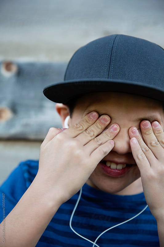 Young boy listening to music and having fun while covering his eyes by Curtis Kim for Stocksy United