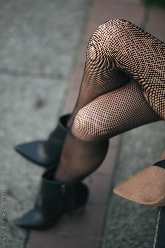 Crossed over legs in fishnet tights by Ania Boniecka for Stocksy United