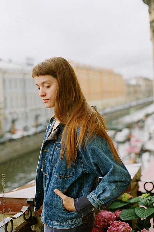 Young woman standing on a balcony by Lyuba Burakova for Stocksy United