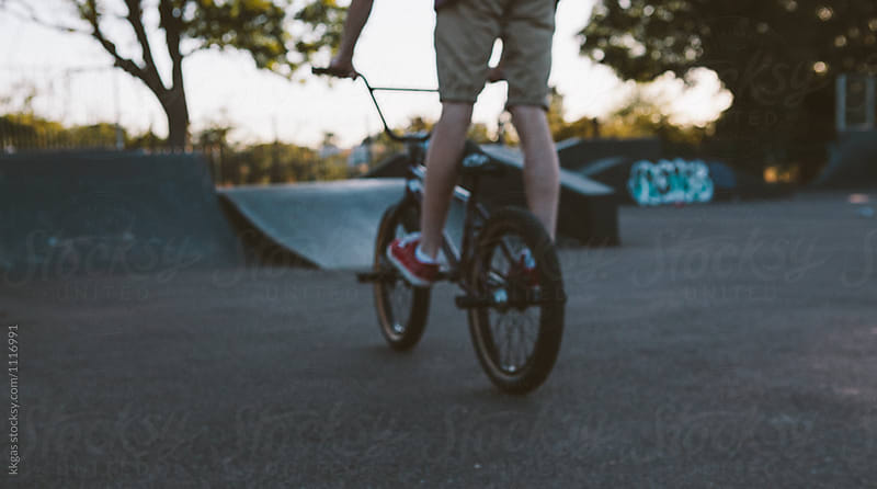 Defocussed shot of a BMX rider performing stunts and tricks on ramps in a skate park