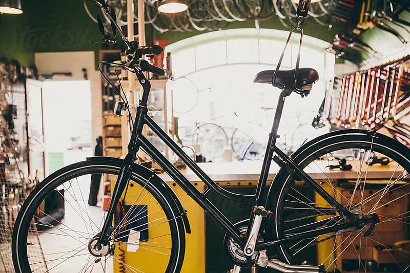 Black bicycle hanging in a cycling shop by Lior + Lone for Stocksy United
