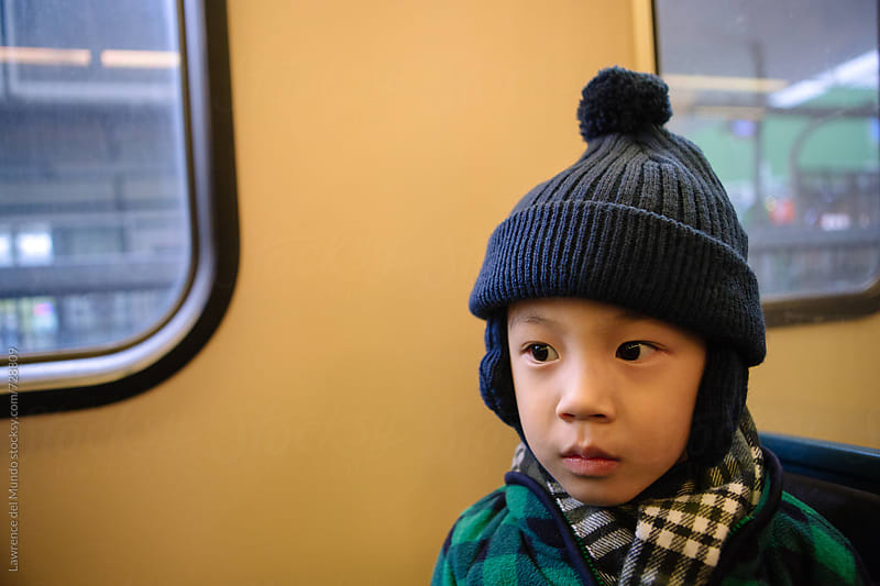 Young kid, with puzzled look inside a train, is riding the train for the first time  by Lawrence del Mundo for Stocksy United