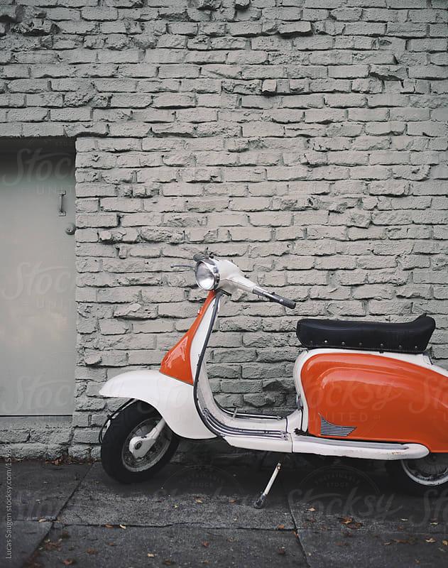 Orange scooter sitting on a city sidewalk. by Lucas Saugen for Stocksy United