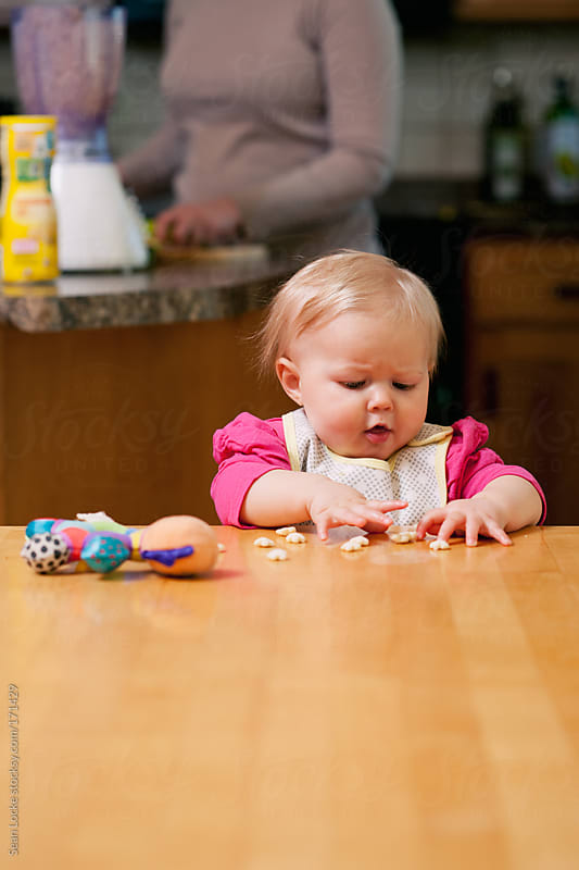 Baby: Baby Eats Cereal While Mother Makes Meal by Sean Locke for Stocksy United