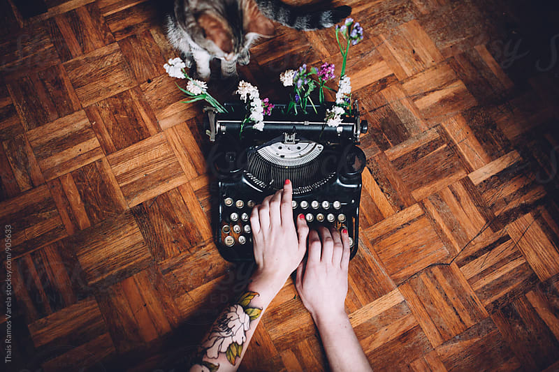 writting machine with flowers and a cat  by Thais Ramos Varela for Stocksy United