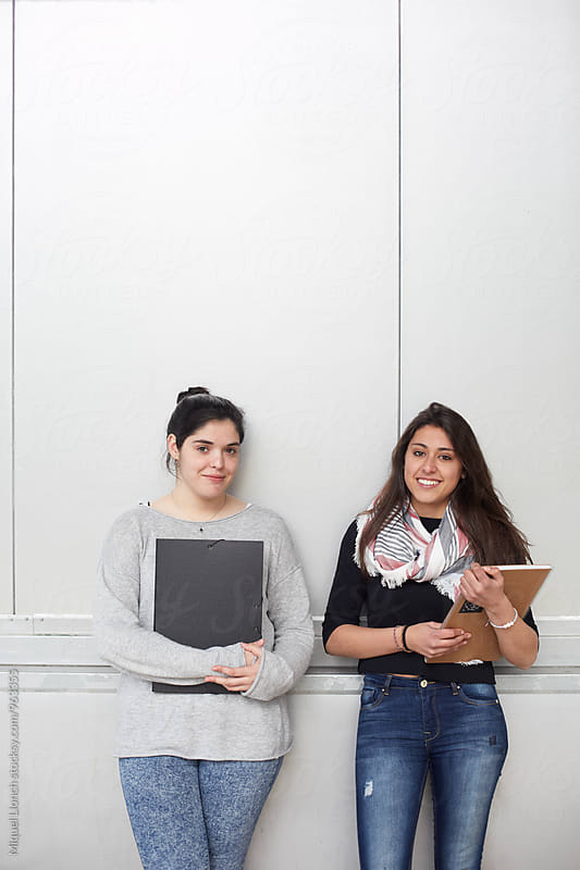 Aware portrait of two young female students with notebooks by Miquel Llonch for Stocksy United