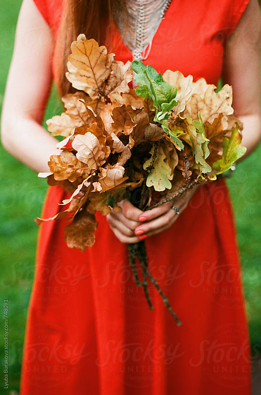 Woman holding bunch of autumn leaves by Lyuba Burakova for Stocksy United