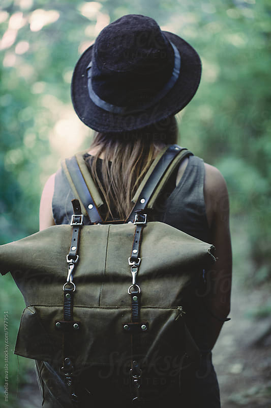 Woman with backpack in the forest, back view by michela ravasio for Stocksy United