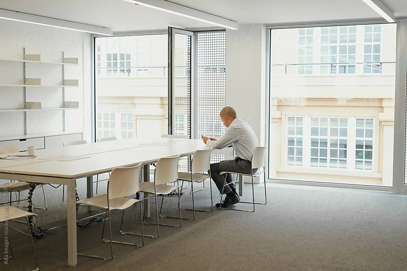 Businessman working alone in boardroom after hours by Aila Images for Stocksy United