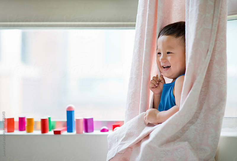 Kid hiding himself by window curtain by Lawren Lu for Stocksy United