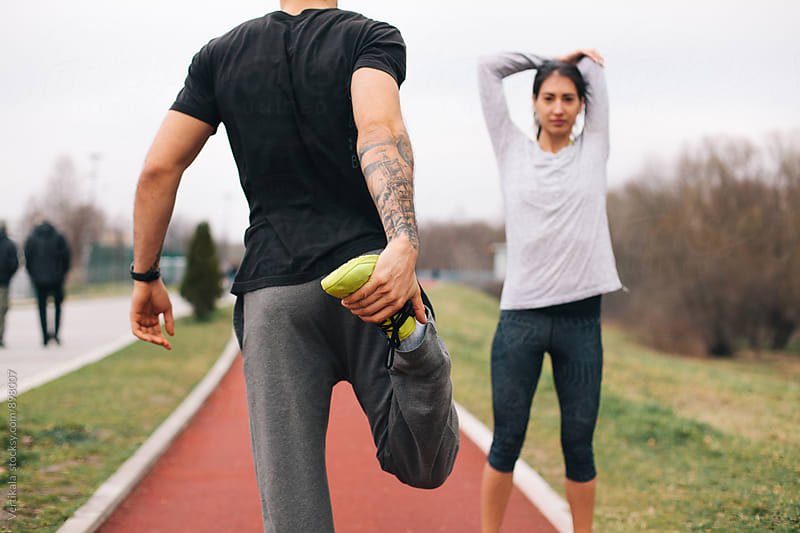 Man and woman preparing for running  by Marija Mandic for Stocksy United
