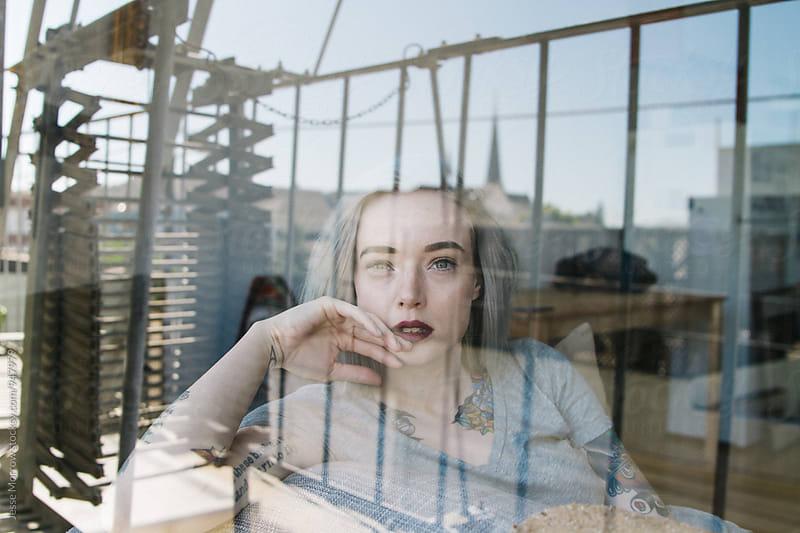 portrait of young female indoors with window reflection on face by Jesse Morrow for Stocksy United