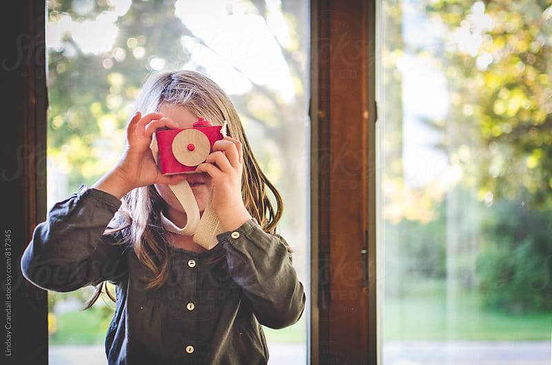 Girl holding toy camera by Lindsay Crandall for Stocksy United
