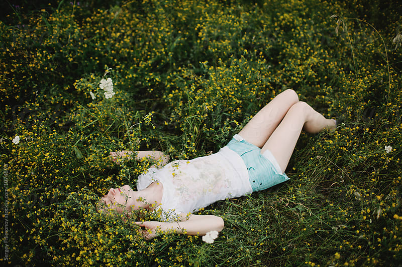 Carefree blonde girl lie down in a yellow flowers by Sergey Filimonov for Stocksy United