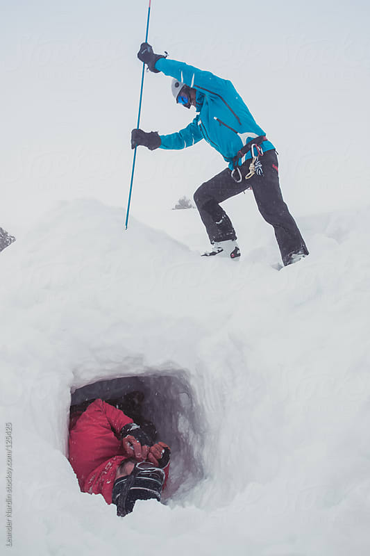freeskier practicing emergency situation with avalanche probe by Leander Nardin for Stocksy United