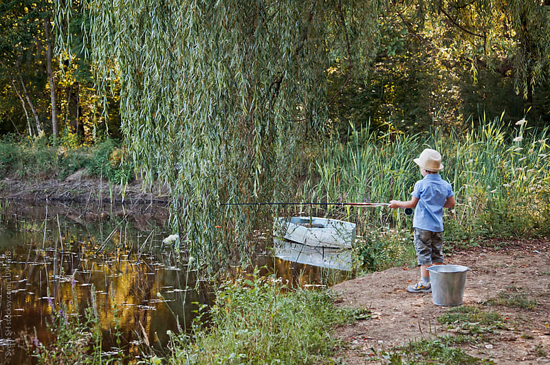 Little boy fishing. by Svetlana Shchemeleva for Stocksy United