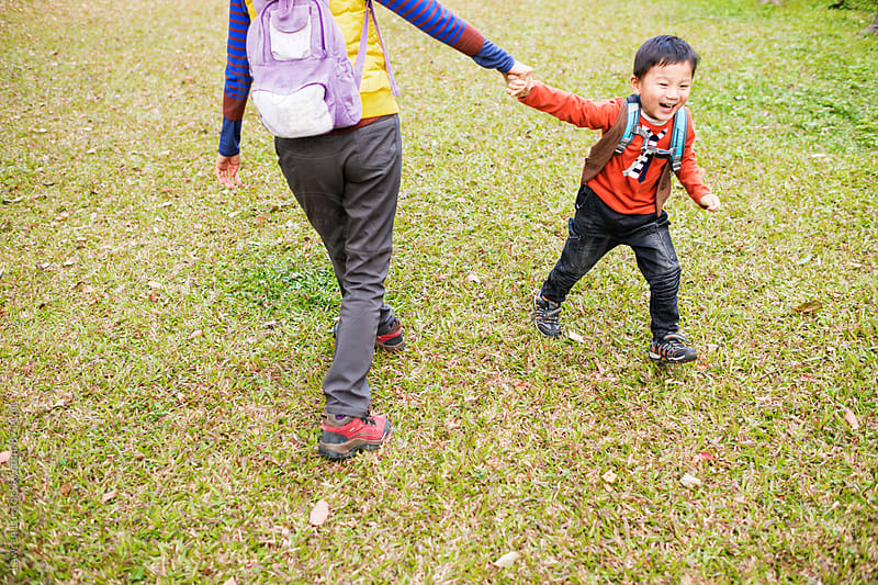 Kid holding mother's hand and running on meadow by Lawren Lu for Stocksy United