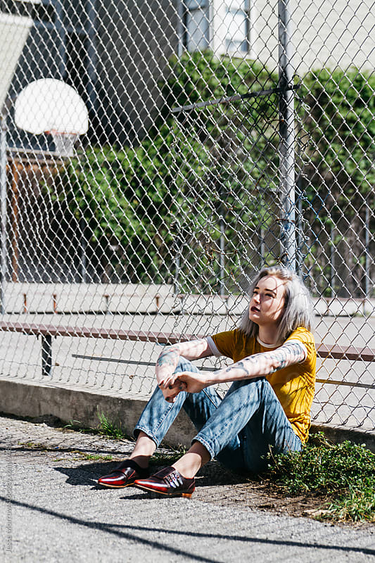 young woman next to basketball court and chain link fence  by Jesse Morrow for Stocksy United