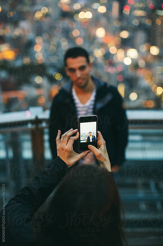 Woman taking a portrait of a man from Tokyo skyline. by BONNINSTUDIO for Stocksy United