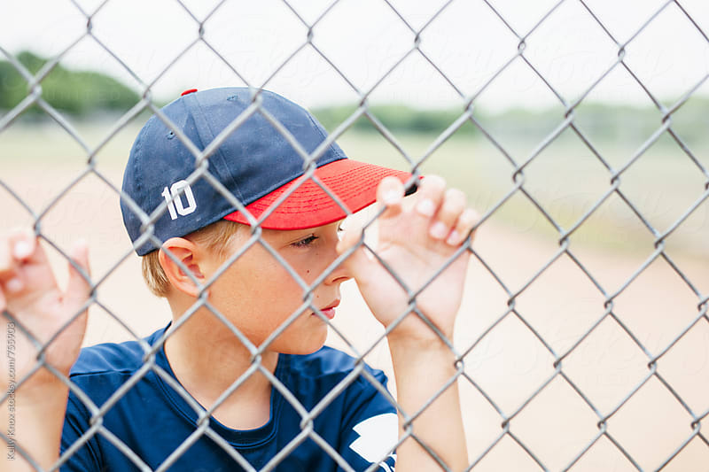 portrait of a young baseball player behind a fence by Kelly Knox for Stocksy United