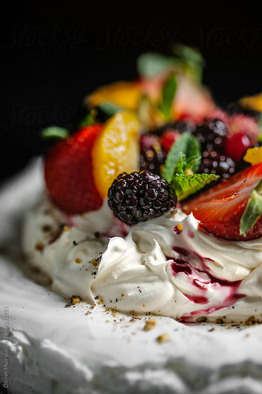 Chantilly cream and summer berries on the top of a meringue nest.  by Darren Muir for Stocksy United