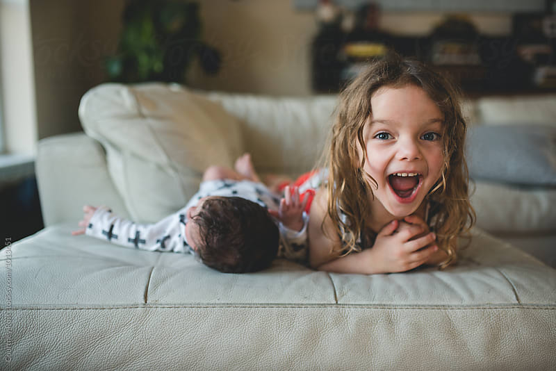 Toddler girl roaring next to new baby by Courtney Rust for Stocksy United