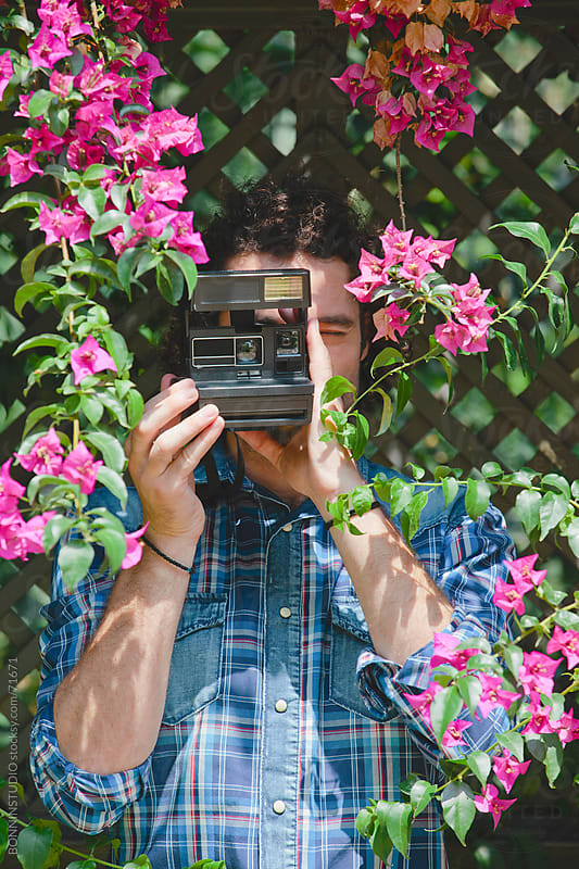 Young man taking photos of flowers with instant camera. by BONNINSTUDIO for Stocksy United