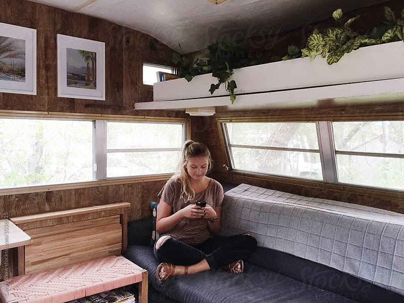 Attractive young woman hanging out in renovated trailer, using her cell phone by Carey Shaw for Stocksy United