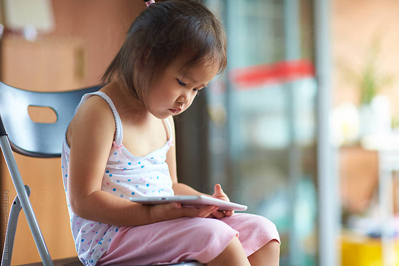 Little girl using tablet indoor by Bo Bo for Stocksy United