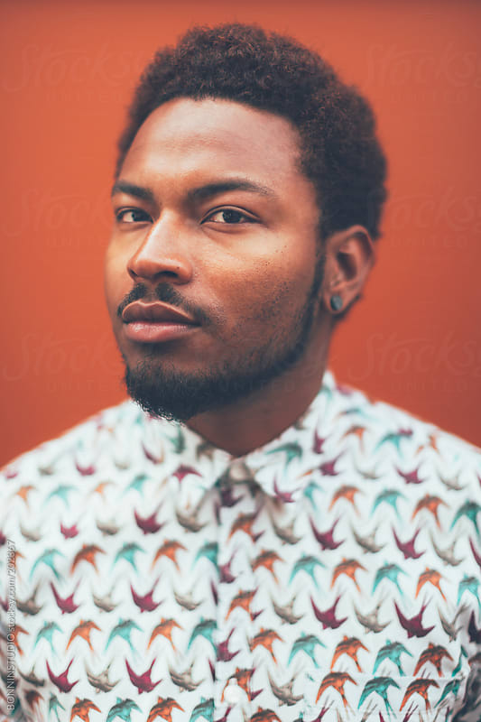 Portrait of modern young black man in front a orange wall. by BONNINSTUDIO for Stocksy United