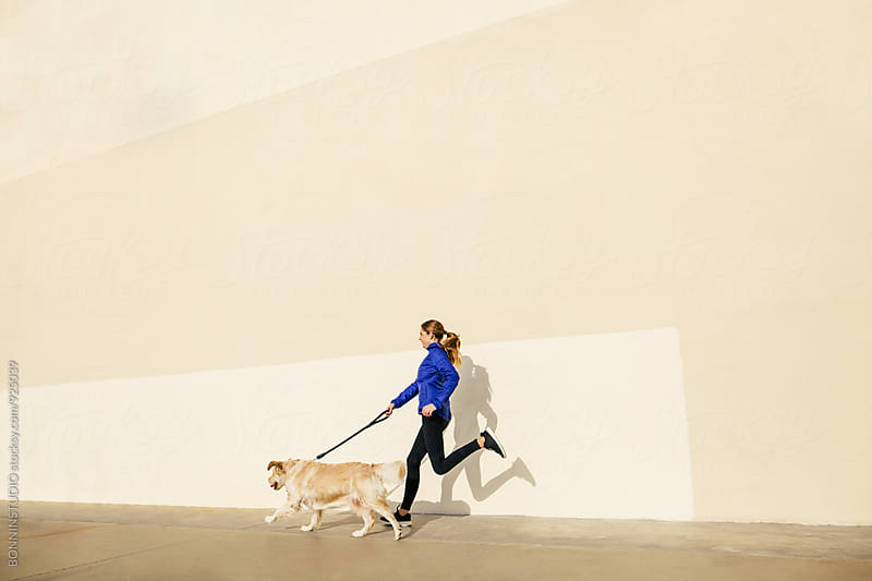 Side view of a woman running with her dog on the street. by BONNINSTUDIO for Stocksy United