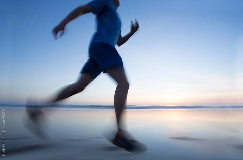 Runner on Beach at sunset. by Hugh Sitton for Stocksy United