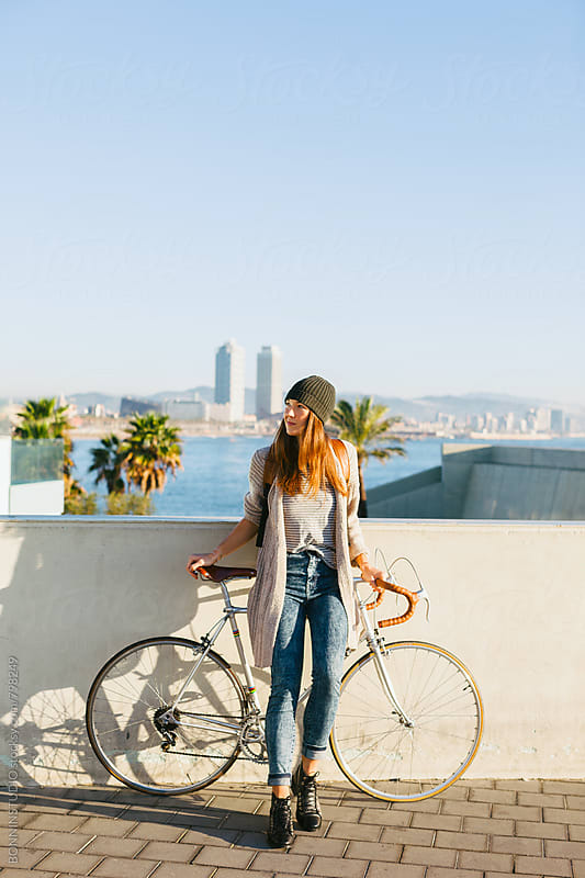 Young woman with her vintage bicycle enjoying a sunny winter day. by BONNINSTUDIO for Stocksy United