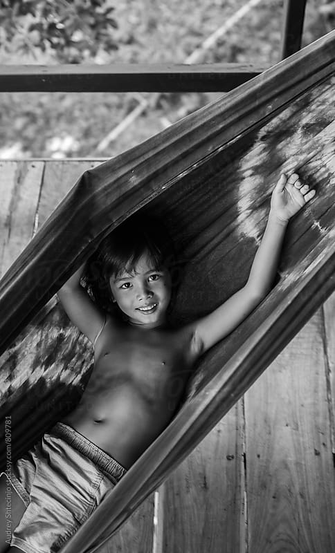 Cute boy relaxing and swinging  in a hammock. by Marko Milanovic for Stocksy United
