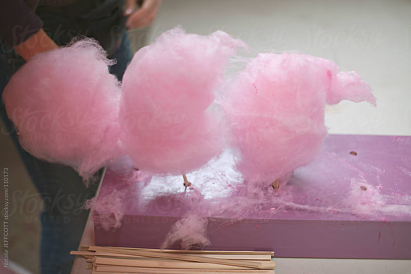 cotton candy / candy floss on table waiting to be sold and eaten by Natalie JEFFCOTT for Stocksy United