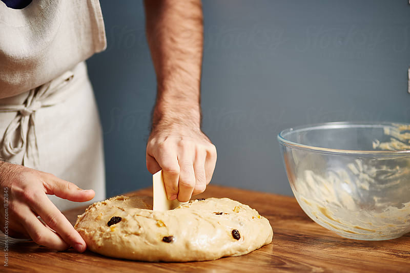 Chef separating dough on wooden table by Martí Sans for Stocksy United