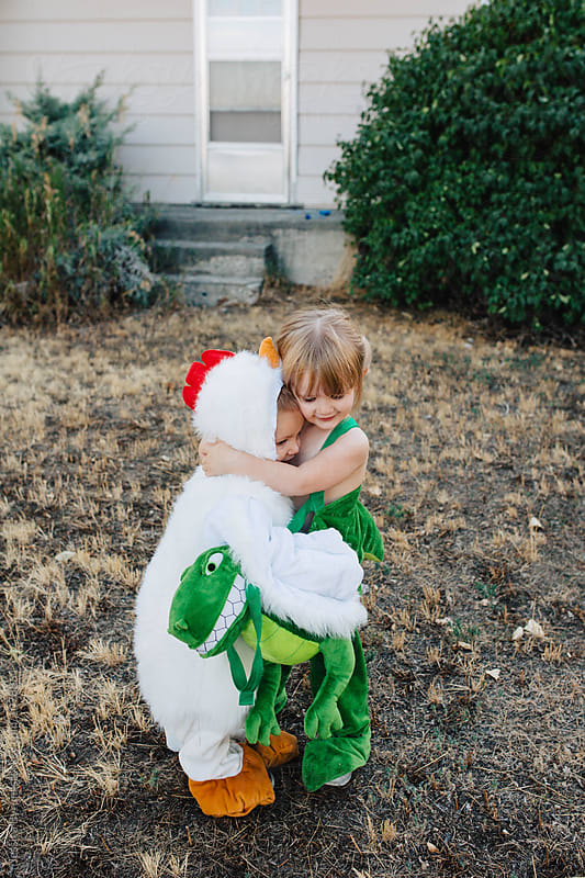 Cute toddler siblings dressed up as a chicken and a dinosaur for Halloween. by Jessica Byrum for Stocksy United