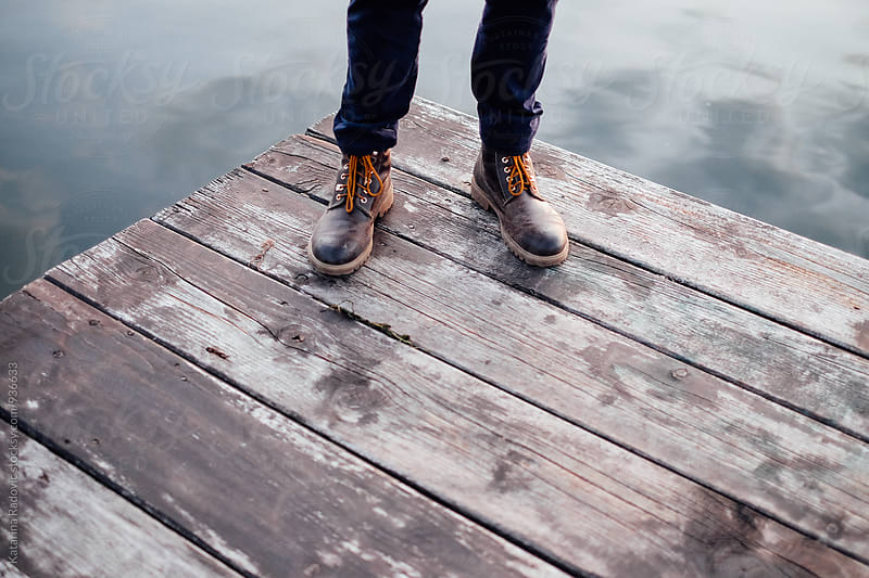 Man in Boots Standing on the Dock  by Katarina Radovic for Stocksy United