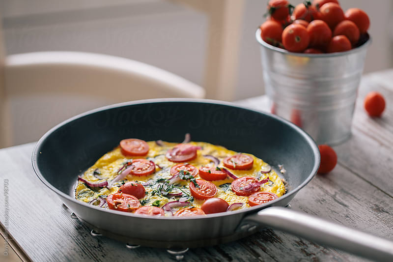 Omelette with cherry tomatoes by Davide Illini for Stocksy United